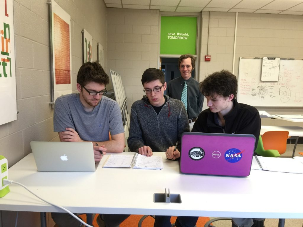 Graham Van Goffrier, Noah Ransom, and Logan Boyd (right to left) participate in the 2016 IEEEXtreme competition. Prof Vince Weaver (background) and Prof Yifeng Zhu (not shown) advised and proctored the competition.,